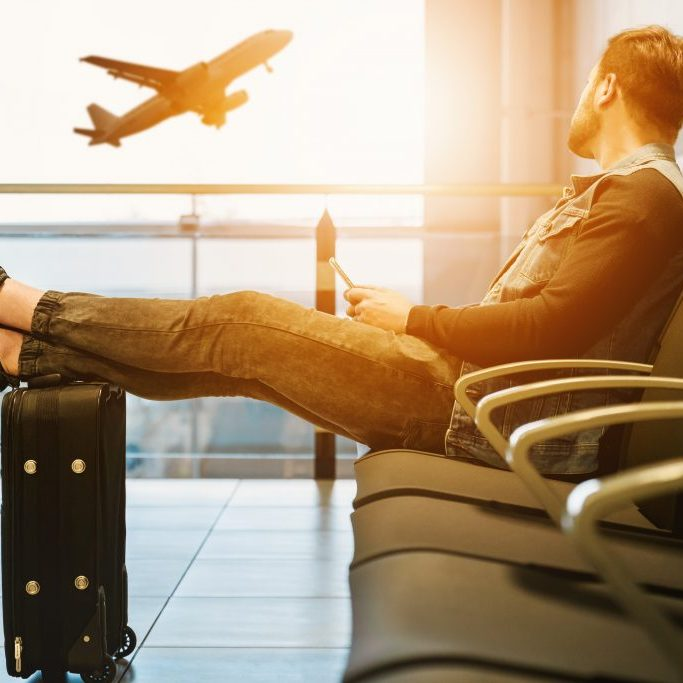 Man sitting at airport with luggage